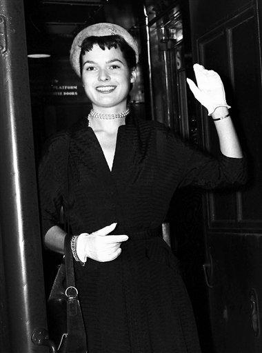 Fashion designer Liz Claiborne waves, in this Aug. 30, 1949 AP file photo, as she arrives at Penn Station in New York en route to Paris for a ten-day trip after winning a Harper's Bazaar-sponsored design contest.