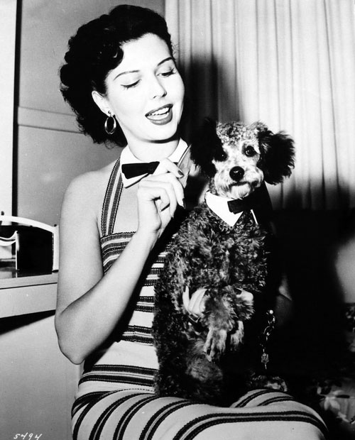 Ann Miller grooms her French poodle Millie during the filming of The Opposite Sex circa 1956